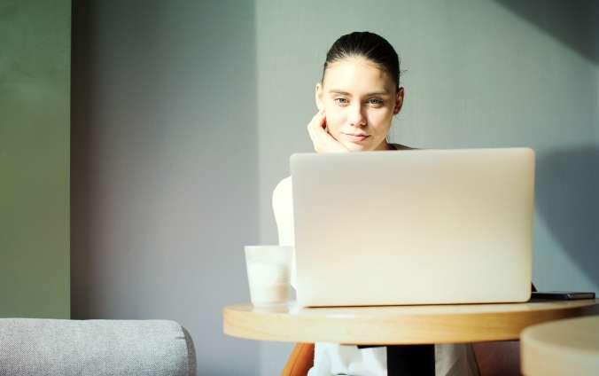 žena sediaca za počítačom a číta si maily