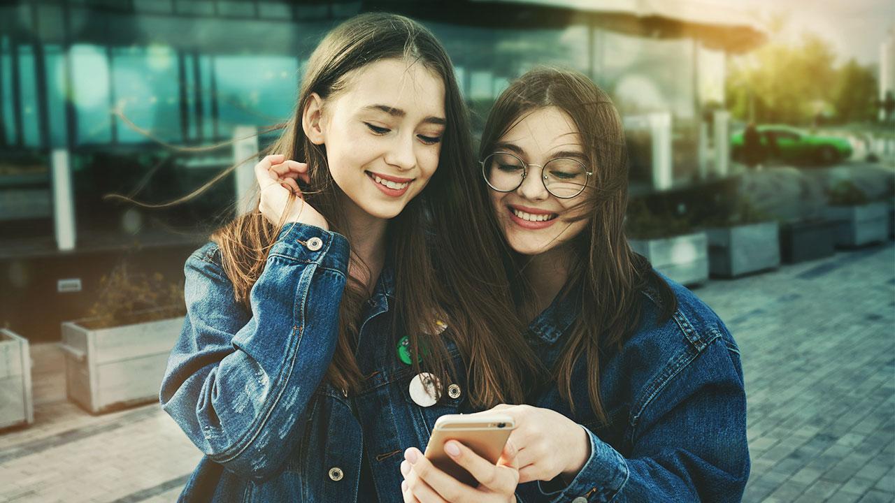 Dievčatá pozerajú do mobilu