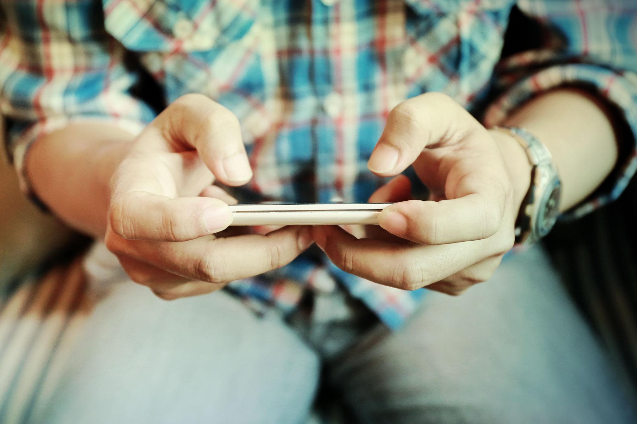 človek drží v ruke telefón